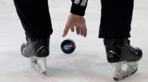 A referee reaches for the puck during the Ice Hockey World Championships group B match between Czech Republic and Norway in the AccorHotels Arena in Paris, France, Thursday, May 11, 2017. (AP Photo/Petr David Josek)