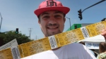 Austin Robertson from Kingston, Ont., holds up four tickets for the Tragically Hip's last show at Rogers K-Rock Centre in Kingston, Ont., on Friday 19, 2016. Ontario will announce reforms to ticket selling legislation on Monday. THE CANADIAN PRESS/Lars Hagberg