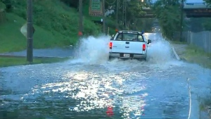A vehicle negotiates a flooded road after heavy rains Friday June 23, 2017.