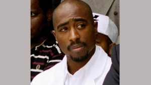 In this Aug. 15, 1996, file photo, rapper Tupac Shakur attends a voter registration event in South Central Los Angeles. A music journalist has filed an infringement lawsuit against the creators of the new Tupac Shakur biopic, claiming that portions of the film are based on his interviews with the late rapper. Plantiff Kevin Powell claims in documents filed Friday, June 23, 2017 that 'All Eyez On Me' borrows from articles he wrote and interviews he had done with Shakur in the 1990s for Vibe magazine. (AP Photo/Frank Wiese, File)