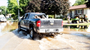 A truck drives down Young Street while firefighters and volunteers pump out people's flooded basements in Harriston, Ont., Saturday, June 24, 2017. The extreme water levels flooded dozens of basements and a Public Works Department building. THE CANADIAN PRESS/Adam Gagnon
