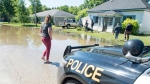 Residents gather on a neighbour's lawn to catch up on the latest news about a flood in Harriston, Ont., Saturday, June 24, 2017. Ontario conservation authorities say the provincial government has cut their funding for flood management programs in half. THE CANADIAN PRESS/Adam Gagnon