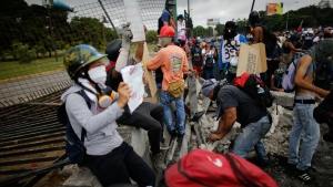 Demonstrators break up concrete to make missiles, from the fence of La Carlota Air Base during a protest on the Francisco Fajardo highway, outside in Caracas, Venezuela, Saturday, June 24, 2017. Demonstrators took to the streets asking restraint from security forces after more than 70 people have been killed during almost 90 days of protests seeking President Nicolas Maduro's removal. (AP Photo/Ariana Cubillos)