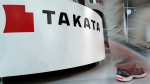 In this May 10, 2017 photo, a visitor walks past the logo of Takata Corp. at a Toyota showroom in Tokyo.  (AP Photo/Shizuo Kambayashi)