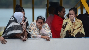 People who survived a sunken ferry, cry as they wait for more information about their missing friends and relatives, at a reservoir in Guatape, Colombia, Sunday, June 25, 2017. (AP Photo/Luis Benavides)