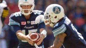 Toronto Argonauts quarterback Ricky Ray hands off the ball to running back Brandon Whitaker (3) in CFL action against the Hamilton Tiger-Cats in Toronto on Sunday, June 25, 2017. THE CANADIAN PRESS/Frank Gunn