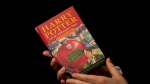"""Sotheby's director of the department of printed books and manuscripts Dr Philip Errington poses for photographers with a first edition copy of the first Harry Potter book """"Harry Potter and the Philosopher's Stone.""""  (AP Photo/Matt Dunham)"""