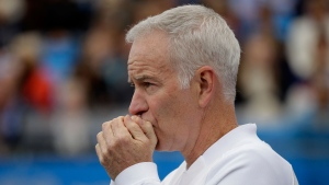In a Saturday June 18, 2016 file photo, John McEnroe, Coach to Canada's Milos Raconic, looks across the court as Raconic plays Australia's Bernard Tomic during their semifinal tennis match on the sixth day of the Queen's Championships London. (AP Photo/Tim Ireland, File)