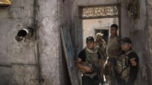 Iraqi special forces soldiers stand in a house retaken by Iraqi forces during fighting against Islamic State militants in the Old City of Mosul, Iraq, Tuesday, June 27, 2017. An Iraqi officer says counterattacks by Islamic State militants on the western edge of Mosul have stalled Iraqi forces' push in the Old City, the last IS stronghold in the city. (AP Photo/Felipe Dana)