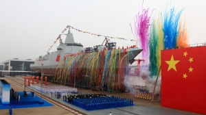 In this photo released by Xinhua News Agency, fireworks explode next to China's new domestically-built 10,000-ton Type 055 destroyer during a launching ceremony at Jiangnan Shipyard in Shanghai, China, Wednesday, June 28, 2017. China's increasingly powerful navy launched its most advanced domestically produced destroyer on Wednesday, at a time of rising competition with other naval powers such as the United States, Japan and India. (Wang Donghai/Xinhua via AP)