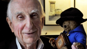 In this June 12, 2015 file photo, Michael Bond poses with a soft toy version of Paddington bear. Publisher HarperCollins says Michael Bond, creator of globe-trotting teddy Paddington bear, died on Tuesday June 27, 2017, aged 91. (Nick Ansell/PA via AP)