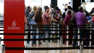 """Travelers wait in line near an Emirates ticket counter at the Seattle-Tacoma International Airport, Monday, June 26, 2017, in Seattle. The U.S. Supreme Court said Monday that President Donald Trump's travel ban on visitors from Iran, Libya, Somalia, Sudan, Syria and Yemen can be enforced if those visitors lack a """"credible claim of a bona fide relationship with a person or entity in the United States,"""" and that justices will hear full arguments in October 2017. (AP Photo/Ted S. Warren)"""