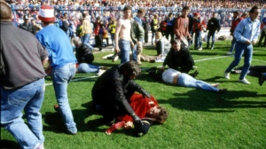 In this April 15, 1989 file photo, police, stewards and supporters tend and care for wounded supporters on the pitch at Hillsborough Stadium, in Sheffield, England. (File Photo/AP)