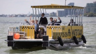Canadian Prime Minister Justin Trudeau sits alongside Ontario Premier Kathleen Wynne, Toronto Mayor John Tory and Toronto Waterfront CEO William Fleissig stands as they arrive in a water taxi on the Toronto waterfront before making a funding announcement on Wednesday, June 28 , 2017. THE CANADIAN PRESS/Chris Young