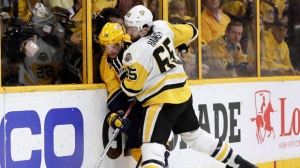 Pittsburgh Penguins' Ron Hainsey (65) checks Nashville Predators' Viktor Arvidsson (38), of Sweden, into the boards during the third period of Game 6 of the NHL hockey Stanley Cup Final, Sunday, June 11, 2017, in Nashville, Tenn. The Toronto Maple Leafs signed veteran defenceman Ron Hainsey to a US$6-million, two-year contract on Saturday. THE CANADIAN PRESS/AP, Mark Humphrey