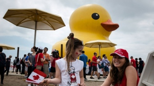 Natalia Belittchenko and her daughter celebrate Canada Day near the giant inflatable duck that sits on Toronto's Harbourfront on Saturday, July 1, 2017. THE CANADIAN PRESS/Christopher Katsarov