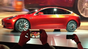 In this March 31, 2016, file photo, Tesla Motors unveils the new lower-priced Model 3 sedan at the Tesla Motors design studio in Hawthorne, Calif. (AP Photo/Justin Pritchard, File)