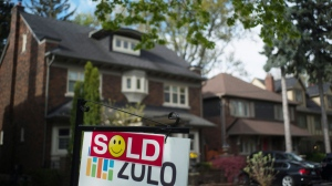 A sold sign is shown in front of west-end Toronto homes, Sunday, May 14, 2017. (Graeme Roy/The Canadian Press)