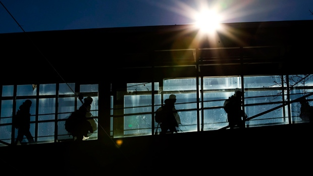 People are silhouetted on a sunny day while they cross between buildings on a pedestrian bridge at Ryerson University in Toronto on Monday, January 12, 2009. THE CANADIAN PRESS/Nathan Denette