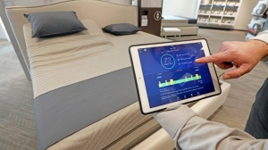 In this Friday, July 7, 2017, photo, Sleep Number store manager Lee Pulliam demonstrates how the company's sleep technology tracks your sleeping patterns, in addition to the other features of the Sleep Number 360 Smart Bed, including a foot warming element, adjustable side comfort, head and foot raising capability and an analysis of how well a person slept. A number of companies are incorporating sleep science into products that help people track and improve the quality of their sleep. (AP Photo/Rogelio V. Solis)