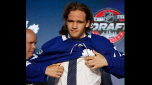 Timothy Liljegren puts on a Toronto Maple Leafs jersey after being selected by the team in the first round of the NHL hockey draft, Friday, June 23, 2017, in Chicago. (AP Photo/Nam Y. Huh)