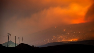 A wildfire burns on a mountain in the distance east of Cache Creek, B.C., in the early morning hours of Monday July 10, 2017. THE CANADIAN PRESS/Darryl Dyck