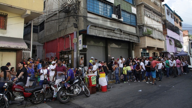 Opposition members line up to cast their ballots at a poll station during a symbolic referendum in Caracas, Venezuela, Sunday, July 16, 2017. Venezuela's opposition called for a massive turnout Sunday in a symbolic rejection of President Nicolas Maduro's plan to rewrite the constitution, a proposal that's escalating tensions in a nation stricken by widespread shortages and more than 100 days of anti-government protests.(AP Photo/Jesus Hernandez)