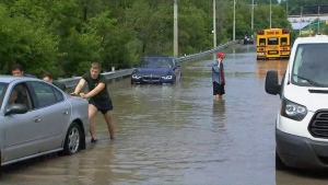 A man is shown pushing a car along a flooded portion of Bayview Avenue on Thursday.