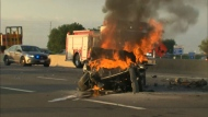 A burning vehicle involved in a collision in the southbound lanes of Highway 400 in Vaughan is pictured Thursday July 20, 2017.