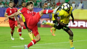 Canada's Michael Petrasso moves to strike the ball as Jamaica's Kemar Lawrence heads it out of the way during a CONCACAF Gold Cup quarterfinal soccer match, Thursday, July 20, 2017, in Glendale, Ariz. Jamaica won the match 2-1 and advances to the semifinal. (AP Photo/Matt York)