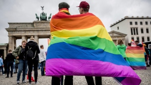 In this June 30, 2017 file photo, men with rainbow flags stand in front of the Brandenburg Gate at an event organized by the Social Democrats to celebrate the legalization of same-sex marriage in Berlin. Germany's president has signed legislation Thursday July 20, 2017 legalizing gay marriage, paving the way for it to take effect this fall. (Michael Kappeler/dpa via AP,file)