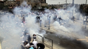 Palestinians run away from tear gas in Jerusalem, Friday, July 21, 2017. An escalating dispute over metal detectors at a contested Jerusalem shrine turned violent on Friday, setting off widespread clashes between Palestinian stone-throwers and Israeli troops. (AP Photo/Mahmoud Illean)