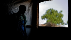 In this Saturday, June 3, 2017 file photo, a South Sudanese refugee and 32-year-old mother, who was raped for several days by a group of soldiers before she was allowed to leave, stands by a window at a women's center focusing on gender-based violence, run by the aid group International Rescue Committee, in Bidi Bidi, Uganda. (AP Photo/Ben Curtis, File)