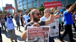"""Activists, one holding today's copy of the Cumhuriyet newspaper, march to a court in Istanbul, Monday, July 24, 2017, protesting against the trial of journalists and staff from the newspaper, accused of aiding terror organizations. Journalists and staff from the Turkish newspaper staunchly opposed to President Recep Tayyip Erdogan have gone on trial in Istanbul, accused of aiding terror organizations - a case that has added to concerns over rights and freedoms in Turkey. The newspaper headline reads in Turkish: """"We Want Justice."""" (AP Photo/Lefteris Pitarakis)"""