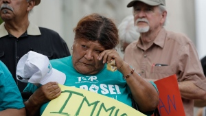 Eldia Contreras wipes away a tear as she takes part in a vigil at San Fernando Cathedral for victims who died as a result of being transported in a tractor-trailer Sunday, July 23, 2017, in San Antonio.  (AP Photo/Eric Gay)