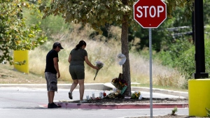 A couple visits a make-shift memorial in the parking lot of a Walmart store near the site where authorities Sunday discovered a tractor-trailer packed with immigrants outside a Walmart in San Antonio, Monday, July 24, 2017.  (AP Photo/Eric Gay)