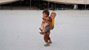 In this Monday, July 24, 2017 photo, a child who fled fighting in Raqqa carries a boy on her back in a refugee camp, in Ain Issa, northeast Syria. The U.S. military is supporting local Syrian forces in a campaign to drive Islamic State group militants from Raqqa. (AP Photo/Hussein Malla)