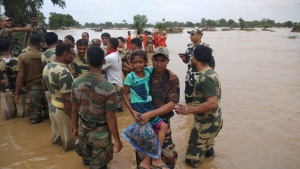India army soldiers rescue flood affected villagers near Shihori in Banaskantha district, Gujarat, India, Wednesday, July 26, 2017. At least 29 people have died in the state of Gujarat amid torrential rains. This week's deaths have taken the toll the state to 83 since the start of the monsoon season which runs from June through September. (AP Photo/Ajit Solanki)