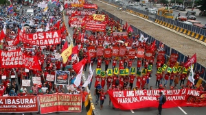 """In this Monday, July 24, 2017, photo, indigenous people known as Lumads, right, form the words """"Save Lumad schools"""" as they join a march of thousands of protesters to coincide with the state of the nation address of Philippine President Rodrigo Duterte in Quezon city, northeast of Manila, Philippines. Human rights groups asked Duterte Wednesday, July 26, 2017, to retract a threat to order airstrikes against tribal schools he accused of teaching students to become communist rebels, warning such an attack would constitute a war crime. U.S.-based Human Rights Watch said international humanitarian law """"prohibits attacks on schools and other civilian structures unless they are being used for military purposes,"""" adding that deliberate attacks on civilians, including students and teachers, """"is also a war crime."""" (AP Photo/Bullit Marquez)"""