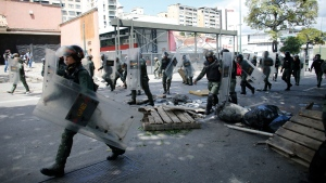 Venezuelan Bolivarian National Guard soldiers break through a barricade set up by anti-government protesters on the first day of a 48-hour general strike in protest of government plans to rewrite the constitution, in the Bello Campo neighborhood of Caracas, Venezuela, Wednesday, July 26, 2017. (AP Photo/Ariana Cubillos)