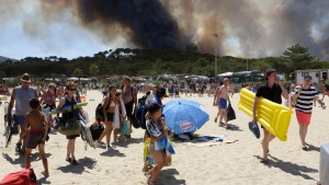 Sunbathers are being evacuated from the beach in Le Lavandou, French Riviera, as plumes of smoke rise in the air from burning wildfires, Wednesday, July 26, 2017. (AP Photo/Claude Paris)