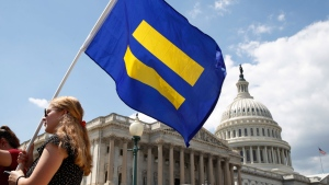 """A supporter of LGBT rights holds up an """"equality flag"""" on Capitol Hill in Washington, Wednesday, July 26, 2017. (AP Photo/Jacquelyn Martin)"""