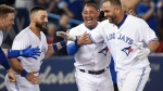 Toronto Blue Jays designated hitter Kendrys Morales, right, is congratulated by teammates Justin Smoak, left to right, Kevin Pillar and Ezequiel Carrera after hitting a walk-off solo home run during ninth inning American League MLB baseball against the Oakland Athletics in Toronto on Wednesday, July 26, 2017. THE CANADIAN PRESS/Nathan Denette