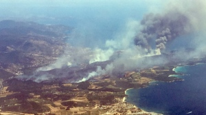 An aerial view shows plumes of smoke rising in the air from burning wildfires in the outskirts of Bormes-les-Mimosas, French Riviera, Wednesday, July 26, 2017. French authorities ordered the evacuation of up to 12,000 people around a picturesque hilltop town in the southern Cote d'Azur region as fires hopscotched around the Mediterranean coast for a third day Wednesday. (AP Photo/Nadine Achoui-Lesage)