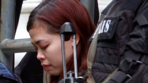 In this March 1, 2017, file photo, Indonesian suspect Siti Aisyah, who is a suspect in the killing of Kim Jong Nam, North Korean leader Kim Jong Un's estranged half brother, is escorted out of court by police officers in Sepang, Malaysia. Two women accused of poisoning Kim in a bizarre airport assassination are expected to plead innocent when they appear in a Malaysian court on Friday, July 28, 2017. Indonesian Siti Aisyah and Vietnamese Doan Thi Huong are suspected of smearing Kim Jong Nam's face with the banned VX nerve agent at a crowded airport terminal on Feb. 13. The women, who face the death penalty if convicted, said they thought they were playing a harmless prank for a hidden-camera show. (AP Photo/Daniel Chan, File)
