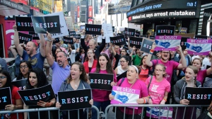 """Protestors gather in Times Square, Wednesday, July 26, 2017, in New York. President Donald Trump declared a ban Wednesday on transgender troops serving anywhere in the U.S. military, catching the Pentagon flat-footed and unable to explain what it called Trump's """"guidance."""" His proclamation, on Twitter rather than any formal announcement, drew bipartisan denunciations and threw currently serving transgender soldiers into limbo. (AP Photo/Frank Franklin II)"""