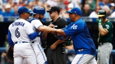Toronto Blue Jays bench coach DeMarlo Hale, right, tries to hold back Blue Jays starting pitcher Marcus Stroman (6) and catcher Russell Martin (55) after they were ejected by umpire Will Little during fifth inning American League MLB baseball action against the Oakland Athletics in Toronto on Thursday, July 27, 2017. THE CANADIAN PRESS/Mark Blinch