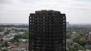 In this Friday, June 16, 2017 file photo, emergency workers walk on the roof of the fire-gutted Grenfell Tower in London, after a fire engulfed the 24-storey building. British authorities say they won't prosecute anyone who unlawfully sublet apartments in the west London tower block before it was devastated by fire. (AP Photo/Matt Dunham, File)