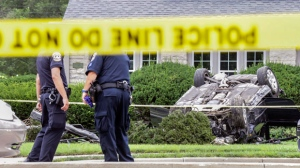 Police examine the scene of a car crash and shooting, Thursday, July 27, 2017 in Indianapolis. A police officer died after being shot multiple times while responding to a traffic crash on the south side of Indianapolis, authorities said Thursday. (Michelle Pemberton/The Indianapolis Star via AP)