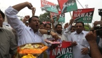 Supporters of opposition parties share sweets to celebrate the dismissal of Pakistani Prime Minister Nawaz Sharif in Peshawar, Pakistan, Friday, July 28, 2017. Pakistan's Supreme Court in a unanimous decision has asked the country's anti-corruption body to file corruption charges against Sharif, his two sons and daughter for concealing their assets. (AP Photo/Muhammad Sajjad)